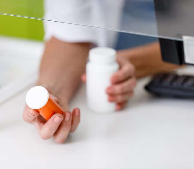 Pharmacist holding out two bottle from counter - TeleLeaf