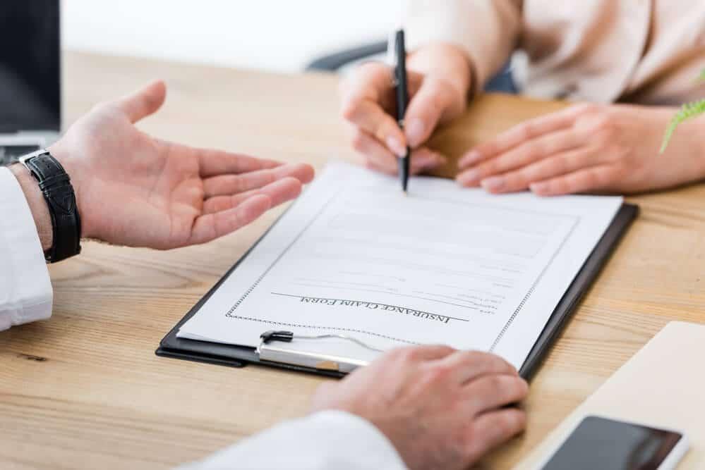 woman signing insurance claim form - Tele Leaf